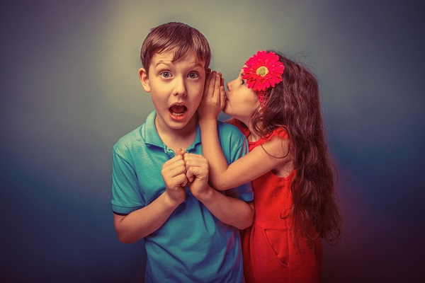 Little girl reaching up to whisper in the ear of a slightly older boy